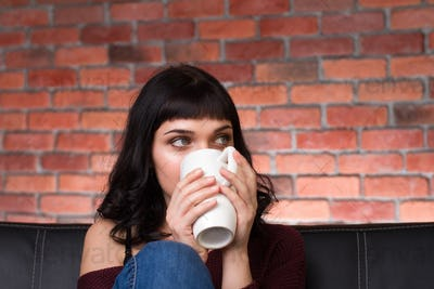 Pretty cute young woman drinking hot tea on sofa