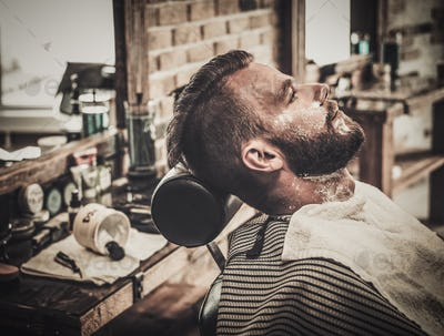 Client during beard shaving in barber shop