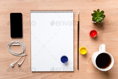 Notepad , paintbrush, paints, smartphone, earphones and cup of coffee
