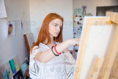 Beautiful pensive young woman painter working in art studio