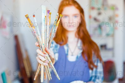 Young woman painter showing dirty paintbrushes in artist workshop