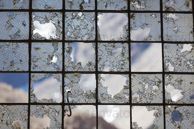 Old Industrial iron window frame rusting with broken glass.