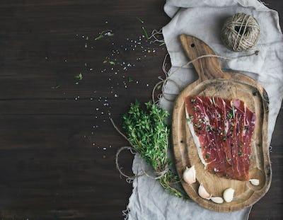 Cured pork meat prosciutto on a rustic woodem board with garli