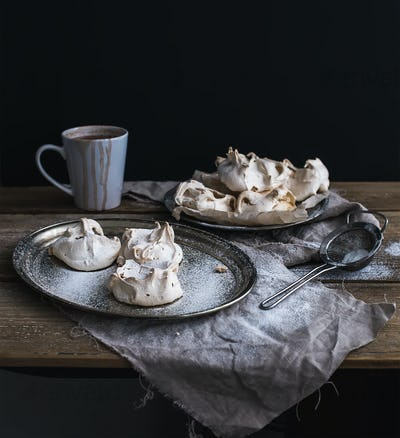White meringue and mug of hot chocolate on a rustic wooden table. Black backdro