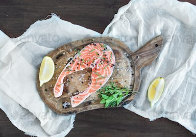 Raw salmon steak with fresh herbs, lemon and spices on rustic wo