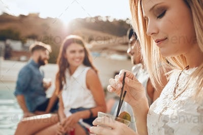 Woman having a drink with friends partying in background