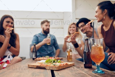 Friends enjoying pizza and drinks in party