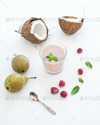 Glass of raspberry, coconut, banana and pear smoothie with fresh mint leaves on white