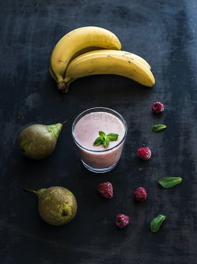 Glass of raspberry and pear smoothie with fresh mint leaves on black