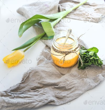 Lemon curd in a jar, bunch of fresh mint and tulip over rustic dark backdrop