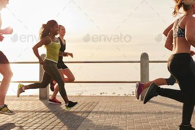 Woman running with friends on seaside promenade