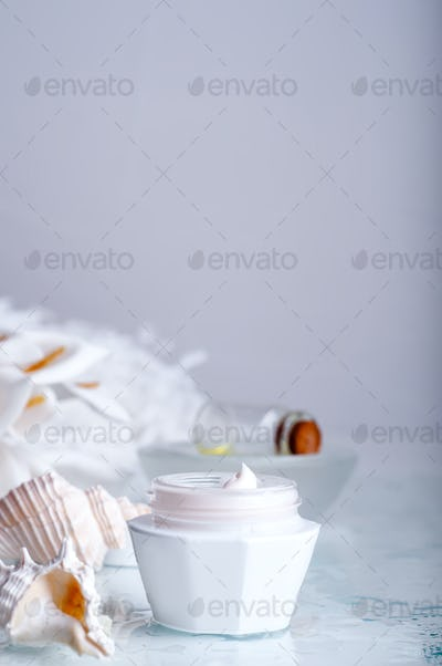 flower and jar of moisturizing face cream for spa treatment.