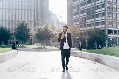 Young handsome caucasian black hair modern businessman walking i