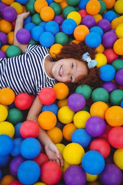 Cute smiling girl in sponge ball pool looking at camera