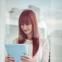 Smiling hipster woman using her tablet in office