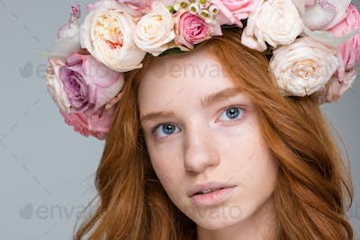 Charming female with red hair in wreath of flowers