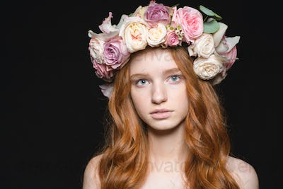 Cute redhead woman with wreath from flowers on head