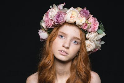 Woman with wreath from flowers on head looking at camera