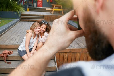 Man photographing his friends with smartphone