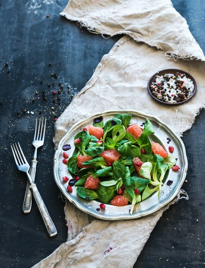 Spring salad with lamb's lettuce, grapefruit, garnet, walnuts and olive oil in vintage metal plate