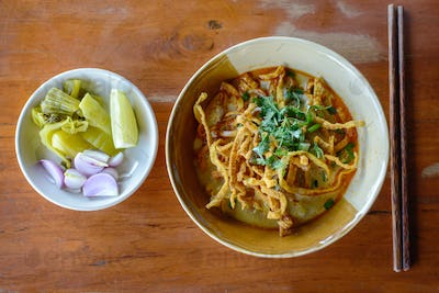 Thai Noodle Curry Soup with pork on wooden table