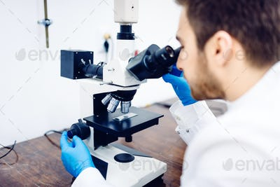 Scientist looking through a microscope in a laboratory, testing samples and probes