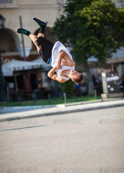 Man doing acrobatic tricks in city street