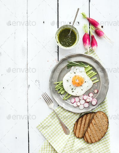 Healthy breakfast set. Fried egg with asparagus, radishes, green sauce and bread