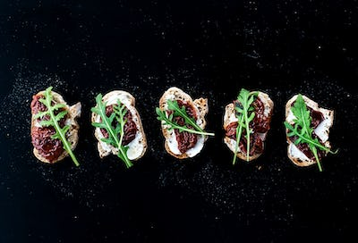 Bruschettas with dried tomatoes, arugula and smoked meat over a black backdrop