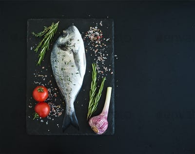 Fresh uncooked dorado or sea bream fish with vegetables, herbs and spices