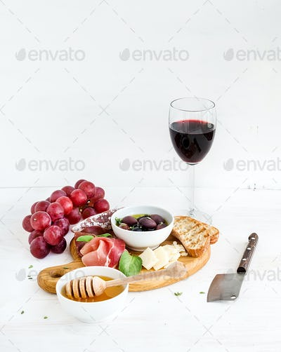 Wine appetizer set. Glass of red, grapes, parmesan cheese, meat variety