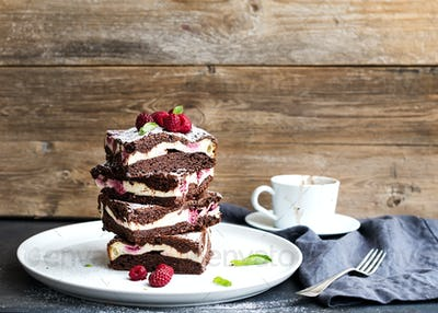 Brownies-cheesecake tower with raspberries on white plate, wooden backdrop, copy space