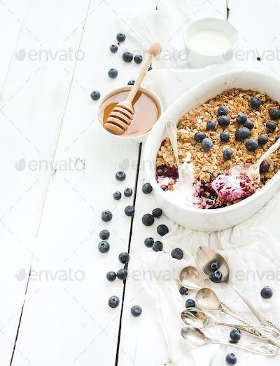 Healthy breakfast. Oat granola berry crumble with fresh blueberries, yogurt and honey