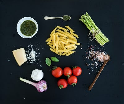 Ingredients for cooking pasta. Penne, green asparagus, basil, pesto sauce, garlic, spices