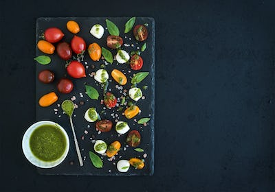 Caprese set. Cherry tomatoes of various color, mozarella, basil leaves, spices and pesto sauce