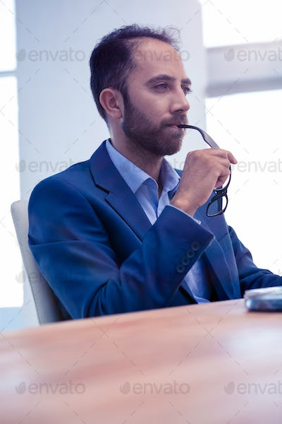 Concentrated businessman holding eyeglasses while sitting at desk in office