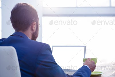 Rear view of business professional holding coffee cup while working on laptop in creative office