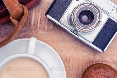 Close-up of old camera with diaries and coffee on table
