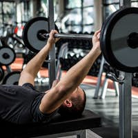 Muscular man lifting barebell while lying on bench at gym