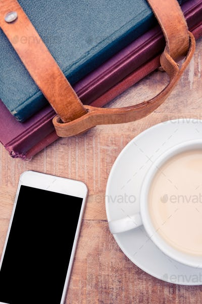 Smartphone with coffee and diaries on table