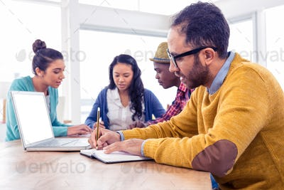 Business man writing in book while sitting with colleagues in creative office