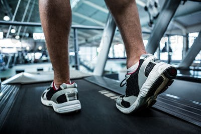 Cropped image of muscular man using treadmill at gym
