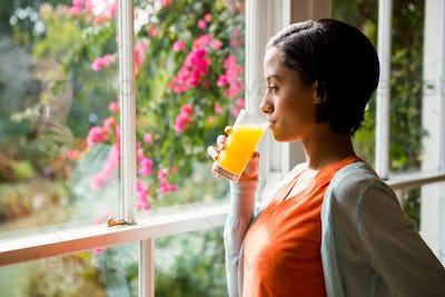 Thoughtful brunette drinking orange juice near the window