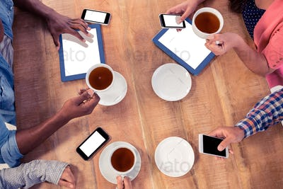 Colleagues using technologies at desk while holding coffee cups in office