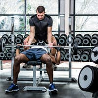 Trainer helping muscular man lifting barebell at gym