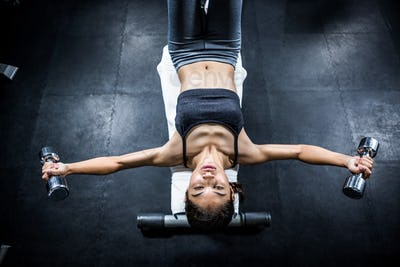 Muscular woman lifting dumbbell while sitting on bench in crossfit