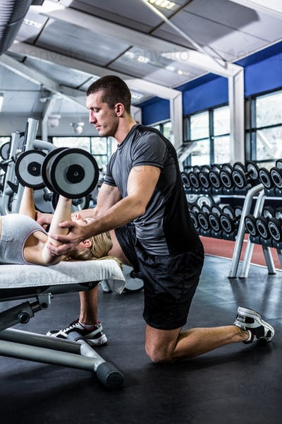 Fit woman doing dumbbells exercise with trainer at gym