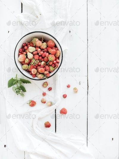 Wild strawberries in rustic metal bowl on white wooden background, top view