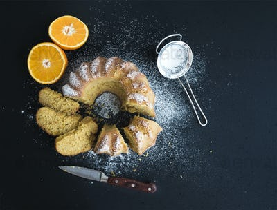 Moist orange bundt yoghurt cake with sugar powder on top, dark grunge background.