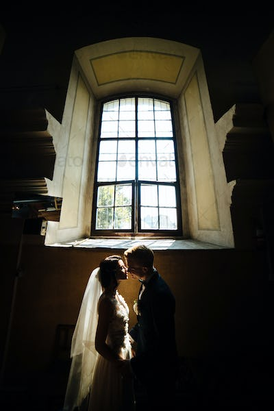 bride and groom on the background of a window.